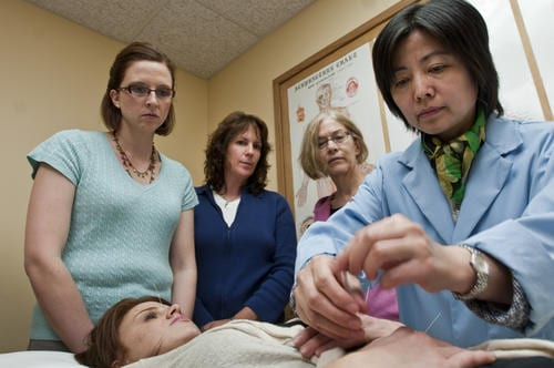 Northwestern Health Sciences University's College of Acupuncture and Chinese Medicine students watch a demonstration of needle placement during class.